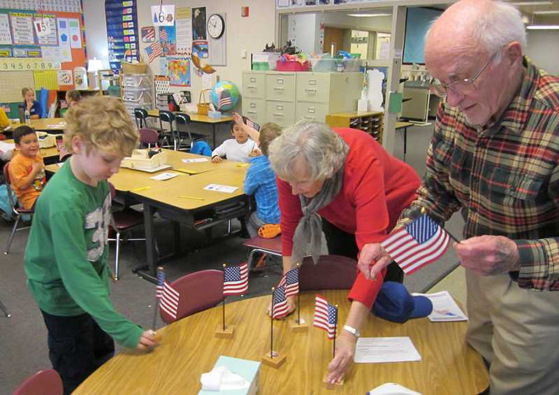 by: BARBARA SHERMAN - PATRIOTIC AND PROUD - Students in Tammy Estrada's first-grade class proudly hold the flags they have just received as King City Lions Janie Berry of Newberg and Rupert Fixott of the Highlands place flags in stands before handing them out to the rest of the class.
