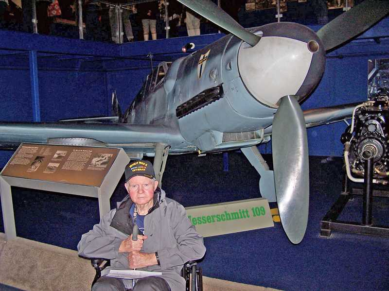 by: STEVE HILL/FOR THE REGAL COURIER - LOTS OF ACTIVITIES - Marion Hill sits in front of a Messerschmitt 109 at Washington, D.C.'s Air and Space Museum, which is the same type of plane that strafed his squadron's airfield in France.