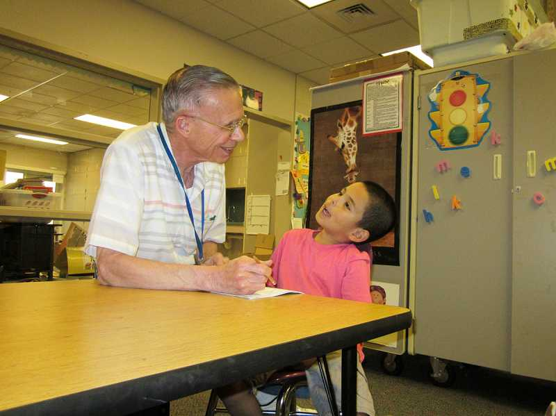 by: BARBARA SHERMAN - GRANDPA KNOWS BEST - 'Grandpa Ernie' Laplace cajoles kindergartner Emi into working through some math problems during a one-on-one session at Deer Creek Elementary in King City.