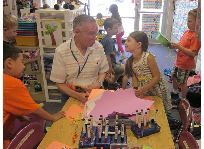 by: BARBARA SHERMAN - UP FOR A GOOD TIME - Volunteer Ernie Laplace talks to an excited Taylor on almost the last day of school at Deer Creek Elementary when the kids found it hard to concentrate.