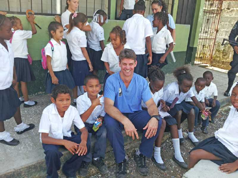 by: COURTESY OF GREG WILLIAMS - TAKING A BREAK - Greg Williams poses with a group of children outside the dental clinic where he and a team set up shop in Honduras.