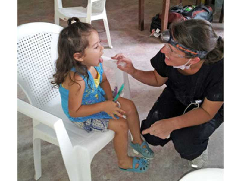 by: COURTESY OF GREG WILLIAMS - ALL IN A DAY'S WORK - Hygienist Rachele Ripp, a member of Greg Williams' dental team, checks a little girl's teeth at one of the clinics that was set up.