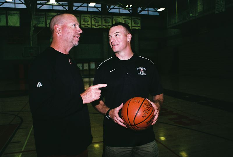 by: JOHN DENNY - Ryan King (right), the new head boys basketball coach at Clackamas High School, strategizes with assistant coach Eddie Wilkins.
