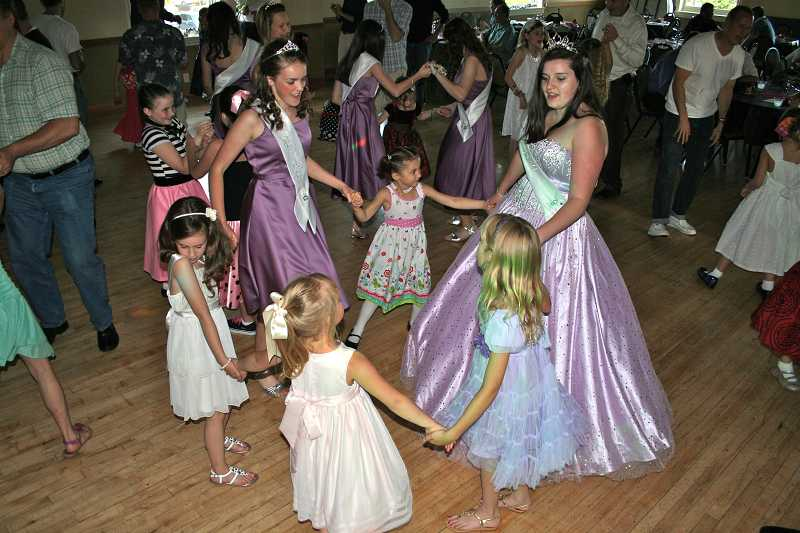 by: J. BRIAN MONIHAN - Two Old Time Fair princesses dance in a circle with younger girls at the Parks and Recreation Daddy-Daughter Dance.