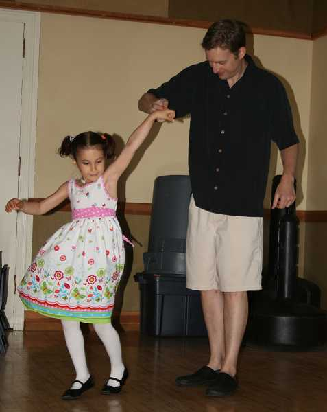by: J. BRIAN MONIHAN - A father shares a tender moment with his daughter, giving her a twirl.