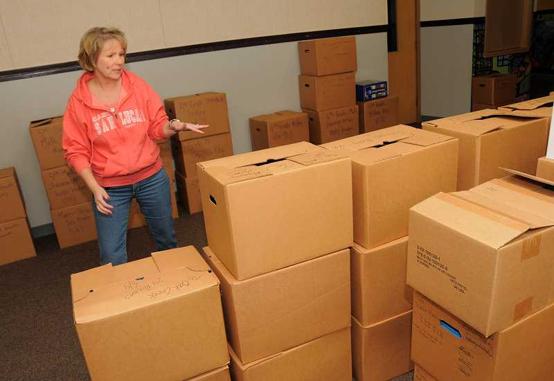 by: VERN UYETAKE - Uplands principal Carol Whitten looks over boxes of books she is sorting to decide which school to send them.