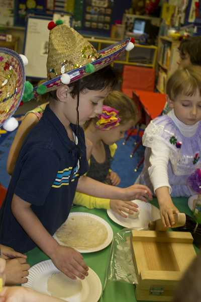Kindergartener Mariano Merlo Flores (center) presses tortillas during the Cinco de Mayo festivities. Next year, first- and second-graders will be able to benefit from educational activities, as well.