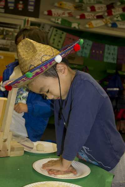 Kindergartener Daniel Shin flattens his tortilla, getting it ready to put in the press. The culture of Spanish-speaking people is incorporated into language immersion lessons.