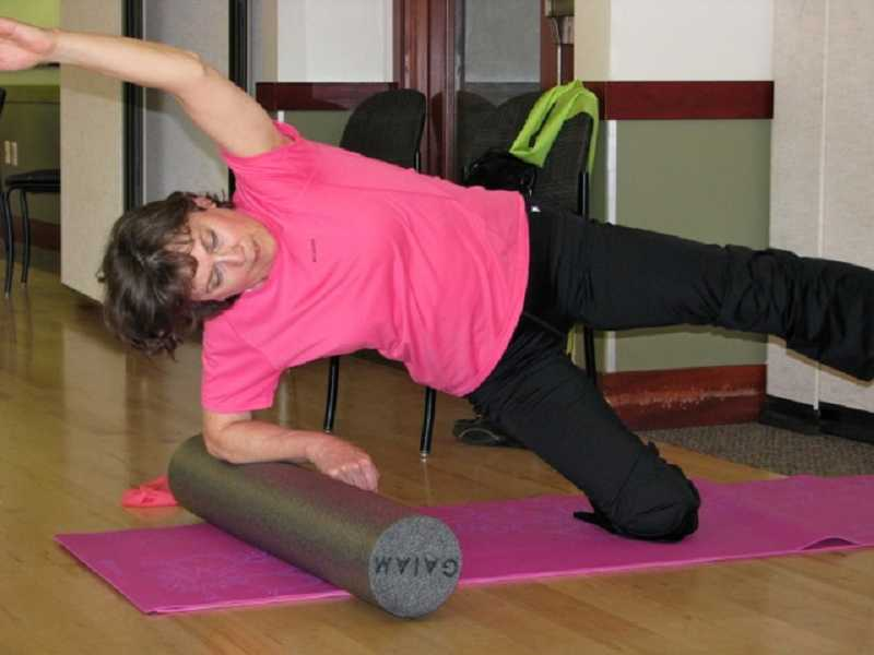 by: SUBMITTED - Deena Westerby balances and stretches across her foam roller at the West Linn Adult Community Center.