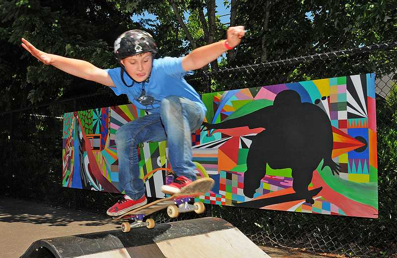 by: VERN UYETAKE - Zach Onustock of Lake Oswego goes flying over a ramp next to one of the newly installed murals.