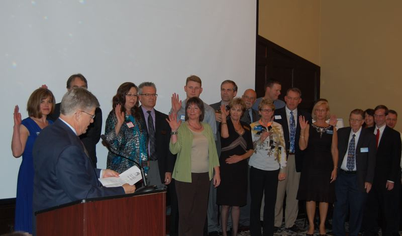 by: PHOTO BY RAYMOND RENDLEMAN - Board members for the North Clackamas County Chamber of Commerce participate in a swearing-in ceremony last week.