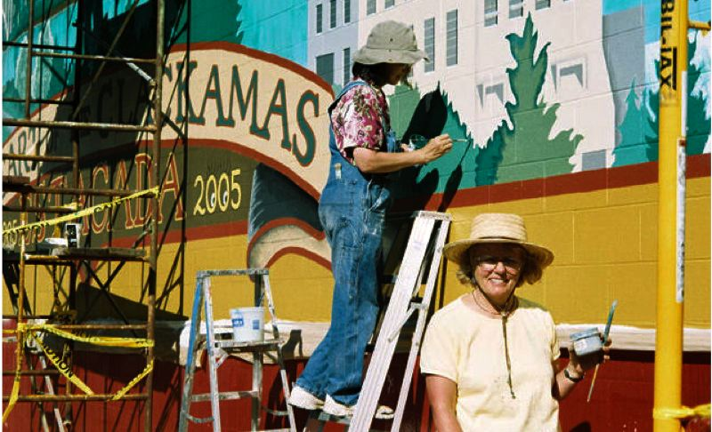 by: SUBMITTED PHOTO - Here Triska (on the ladder) is working on Estacadas bicentennial mural on the side of the Les Schwab building.