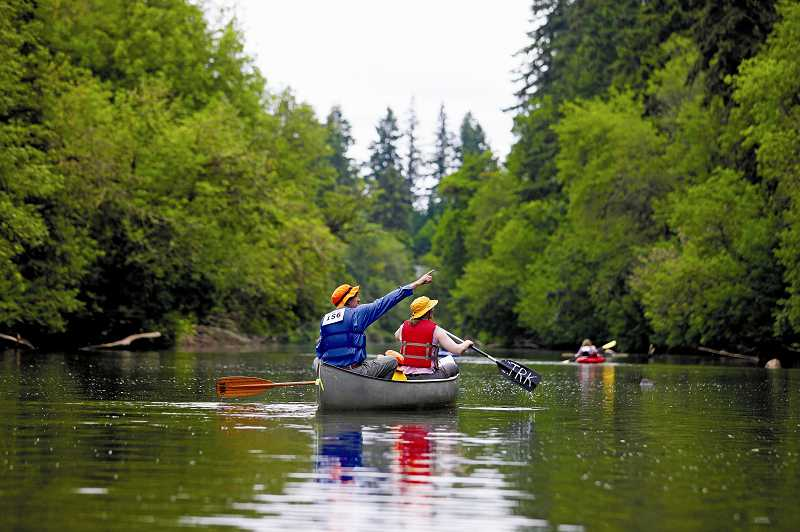 by: JONATHAN HOUSE - Dave Porter points out wildlife along the Tualatin River to his family during the Tualatin Riverkeepers' annual Discovery Day on Saturday.
