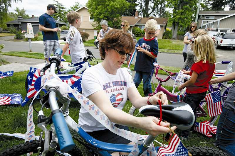 by: JONATHAN HOUSE - After coordinating the Royal Woodlands Children's Fourth of July Parade for five years, Kimarie Wolf, center, has earned the respect of her neighbors as the embodiment of the festive annual event.