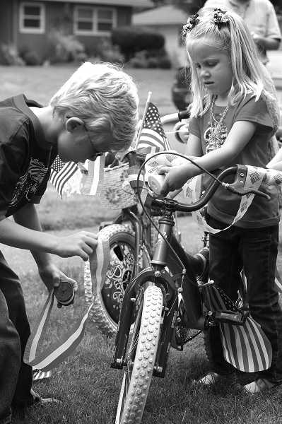 by: JONATHAN HOUSE - Aidan and Audrey Mollenhauer help decorate a bike for the Royal Woodlands Children's Fourth of July Parade on Wednesday.