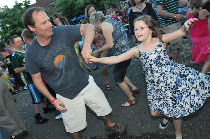 by: VERN UYETAKE - A father and daughter take a spin at West Linn's 2010 street dance.