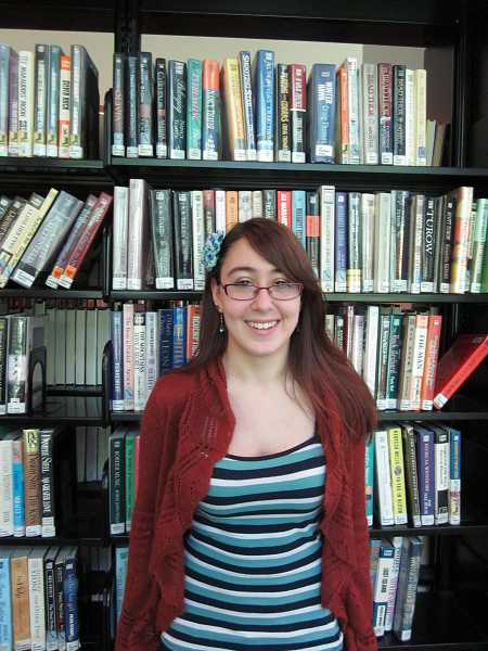 by: KATIE SMITH - Kasey Vestal smiles among the library´s copious book collection, in which she tucks clues for scavenger hunt participants to find.
