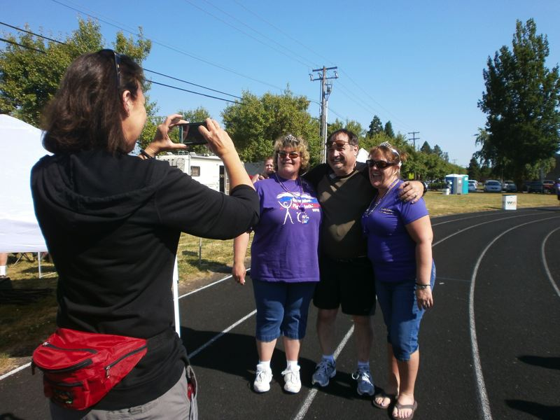 by: PHOTO BY NANCY TOWNSLEY - A Relay attendee snaps a photo of three participants, including Brenda Kintz of Forest Grove (center), who led a new team called Fight Like You Mean It.
