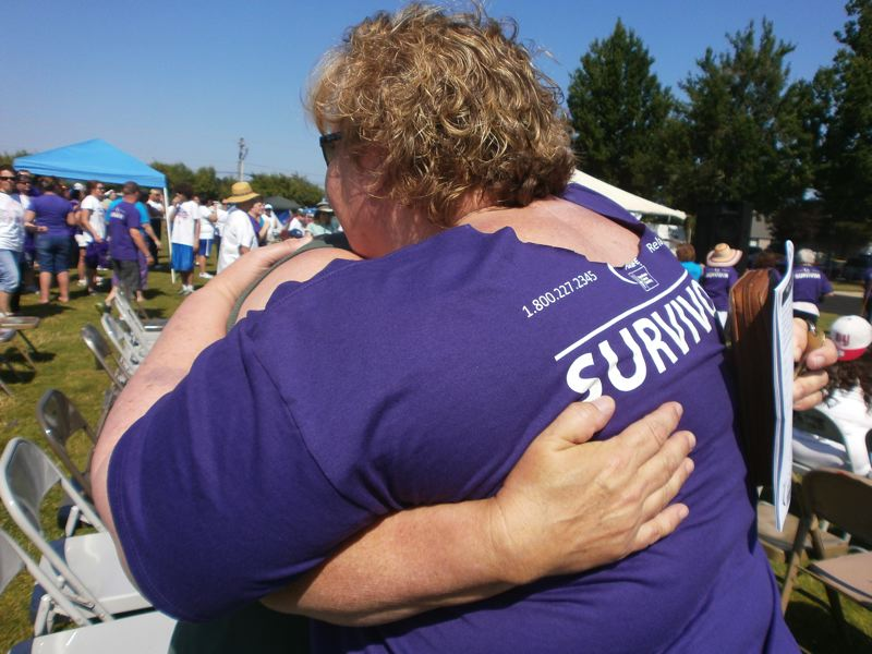 by: PHOTO BY NANCY TOWNSLEY - Emotions play a big role at Relay for Life, particularly when caregivers and friends greet cancer survivors during opening ceremonies.