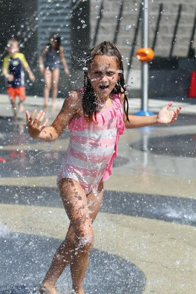 by: JONATHAN HOUSE - Alicia Bozarth runs through streams and waves of water to beat the summer heat at Conestoga's new splash pad.