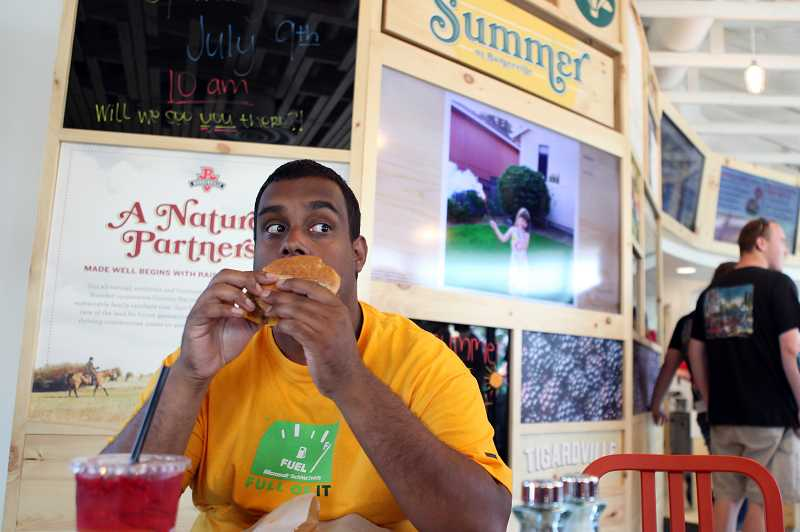 by: JAIME VALDEZ - Paul Wade of Tigard takes a bite of a hamburger at the grand opening of Burgerville along Pacific Highway.