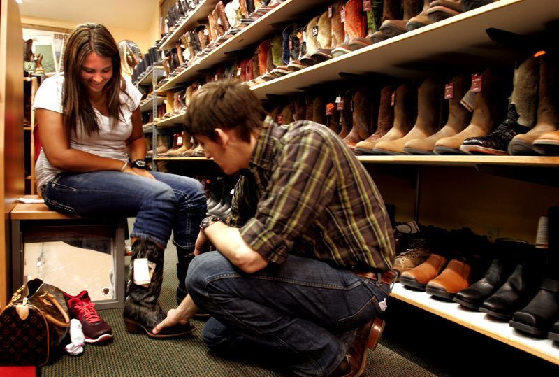 by: PHOTO BY JIM CLARK - Boot Barn assistant manager Ben Kirk helps Katelyn Meeks select a pair of cowboy boots at the Troutdale store.