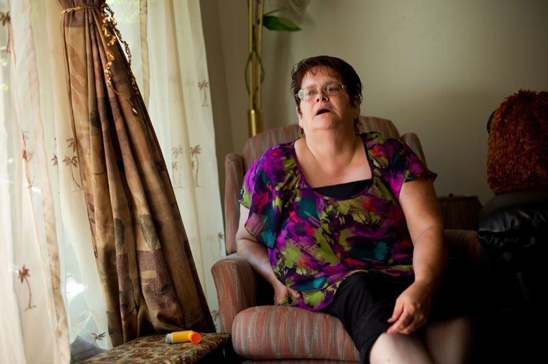 by: CHRISTOPHER ONSTOTT/TRIBUNE PHOTO - Asthma sufferer Linda Monroy tries to breathe in air after using her inhaler. Ten years without health insurance and four years with have made Monroy part of a study that has national  implications.