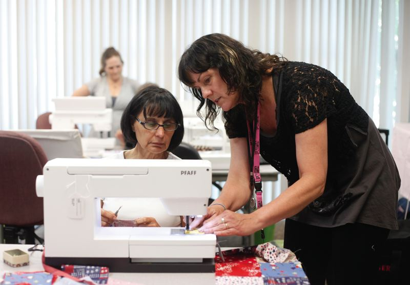 by: JONATHAN HOUSE - Debbie Turner helps Mary Sitas with stitching technique during a meeting of Quilts of Valor at the Montevilla Sewing Center in Portland.