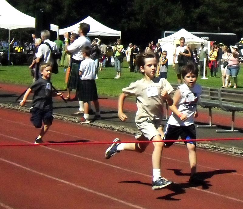 by: PHOTO BY MELISSA ADELE HASKIN - Nathan Fisher, 8, dashes towards the finish line. Fisher won one of the Fun Run races.