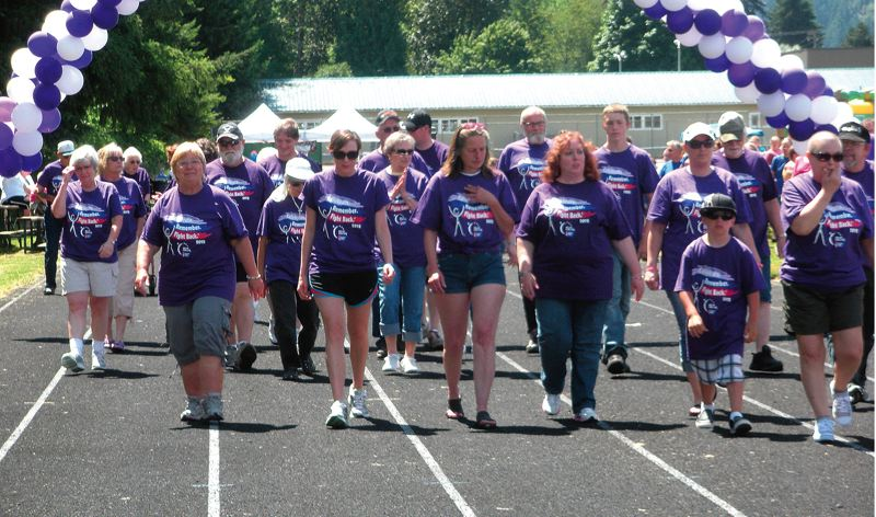 by: STAFF PHOTO BY JIM HART - Cancer survivors begin walking the first lap at the Relay for Life in Estacada at the high school track. The young boy at right is 8-year-old Mikey Miltenberger, who has been cancer free for two years.