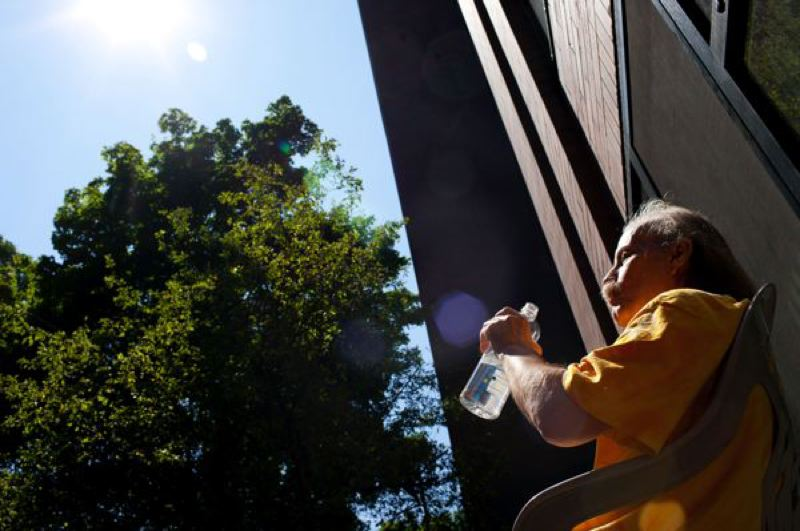 by: CHRISTOPHER ONSTOTT/PAMPLIN MEDIA GROUP - With no air conditioning inside, Jonathan Linneman sips on a water bottle in the courtyard of his Northwest Portland apartment. Much of the center city lies in an urban heat island, with higher than normal temperatures because of an abundance of concrete and asphalt, and a lack of tree canopy.