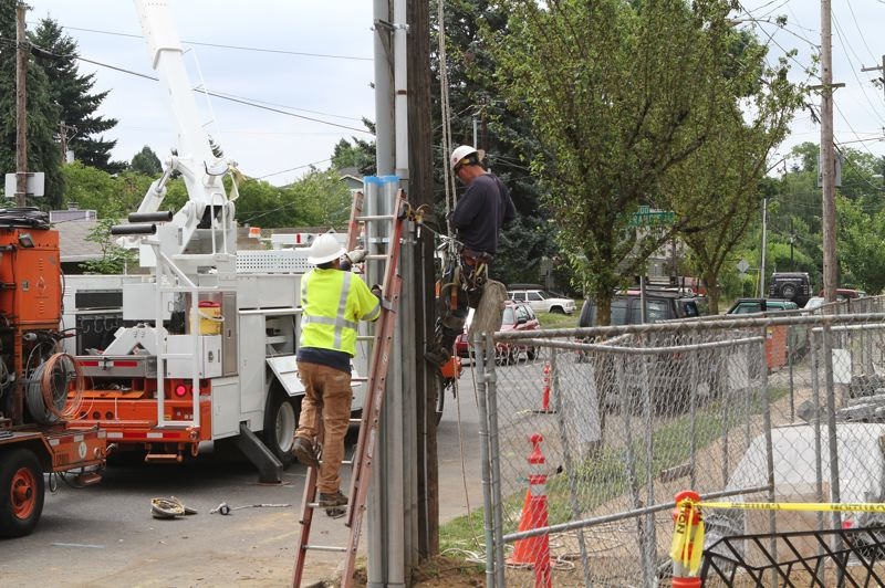 by: DAVID F. ASHTON - A PGE crew finishes hooking up the electricity for the new Dougy Center building.