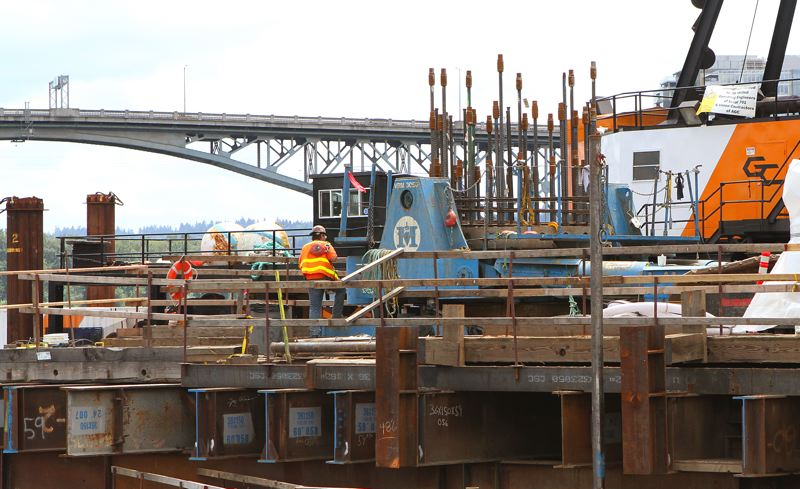 by: DAVID F. ASHTON - The light blue unit holds 'pre-stress' tendons in place, keeping the reinforcing metal under tension while concrete is poured and let to cure. The Ross Island Bridge soars in the background.