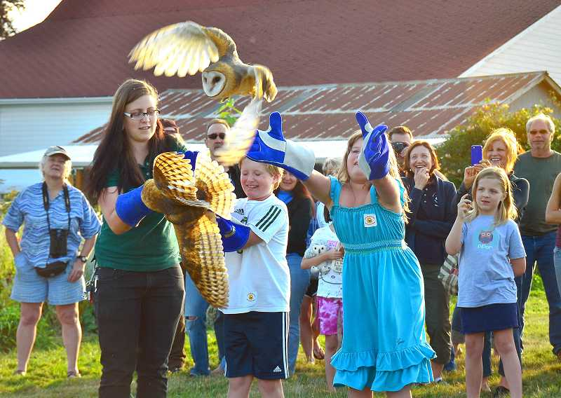 by: VERN UYETAKE - Twins Alex and Annie Davis release an owl, with some help from Lacy Campbell of the Audubon Society of Portland. Alex and Annie are the grandchildren of Karen Davis, garden program coordinator at Luscher Farm.