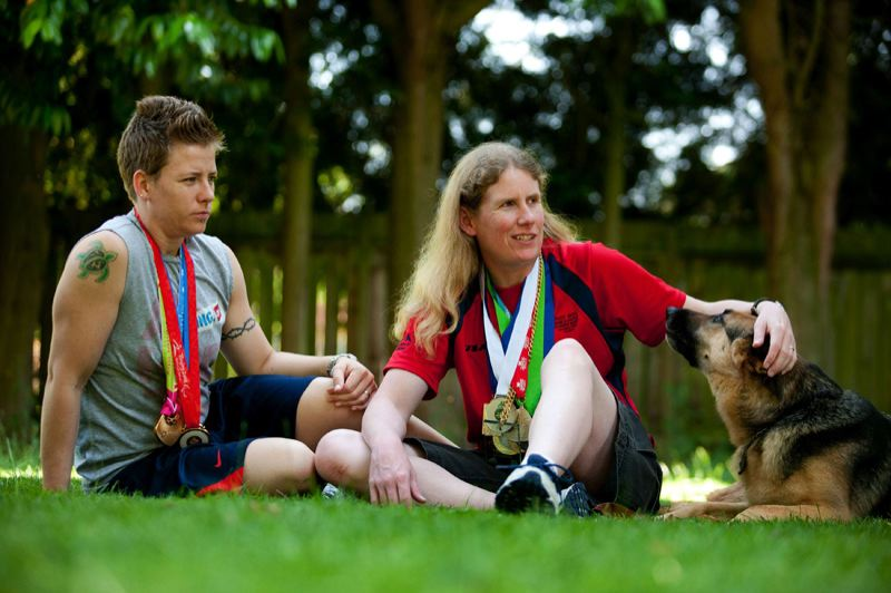 by: TRIBUNE PHOTO: ADAM WICKHAM - U.S. goalball players Asya Miller (left) and Jen Armbruster enjoy a Portland summer day with their German Shepherd, Vail, as they await defense of the Paralympics gold medal in London.