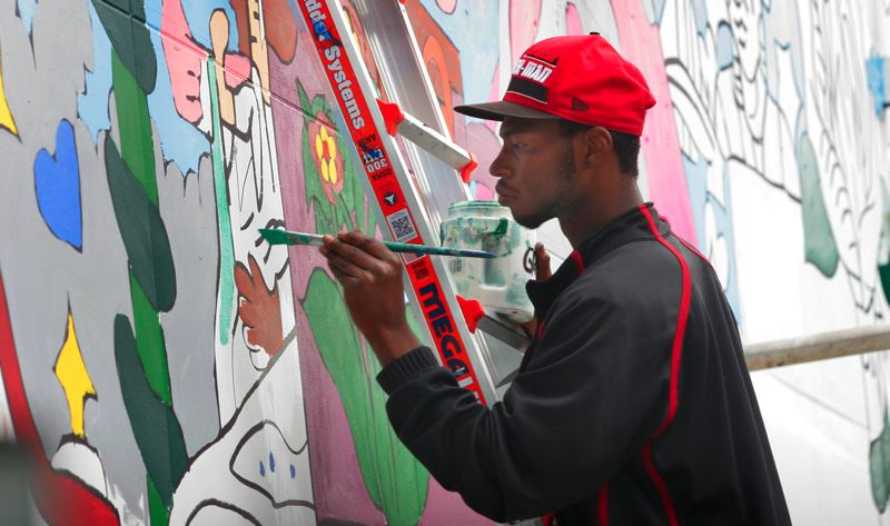 by: JIM CLARK - Antwoine Thomas designed the Rockwood mural. He says if he had to use one word to describe it, it would be 'liberating.' The painting is so brightly colored because Thomas originally drew the design using Sharpies.