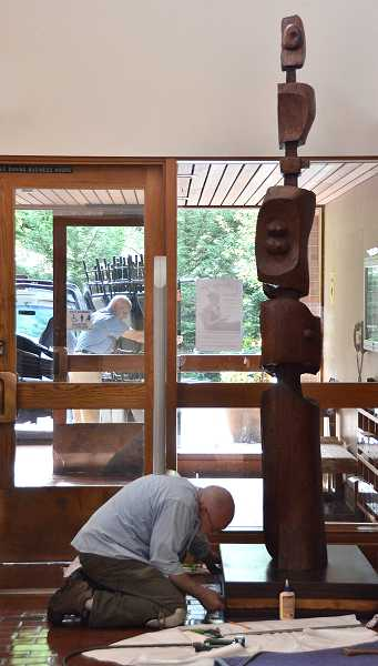 by: REVIEW, TIDINGS PHOTO: VERN UYETAKE - Left: Tom Jones, an expert woodworker and sculpture, repairs a wood sculpture created by LeRoy Setziol at the Lake Oswego Public Library.   REVIEW, TIDINGS PHOTO: VERN UYETAKE