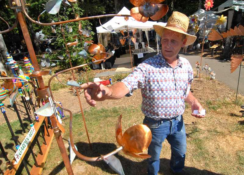 by: VERN UYETAKE - A metal artist showcases his garden art at a past arts festival.