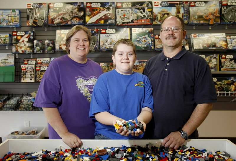 by: JONATHAN HOUSE - Bricks & Minifigs owners Lynnette Scott, left, and Jeff Scott, right, with their son Trevor, are having a grand opening this weekend of their LEGO store in Beaverton.