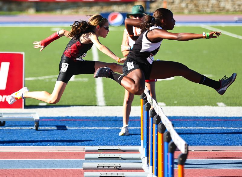 by: DAVID BLAIR - NO STOPPING HER -- Skyler Blair (left) competed in the 80-meter hurdles event despite having a broken arm.