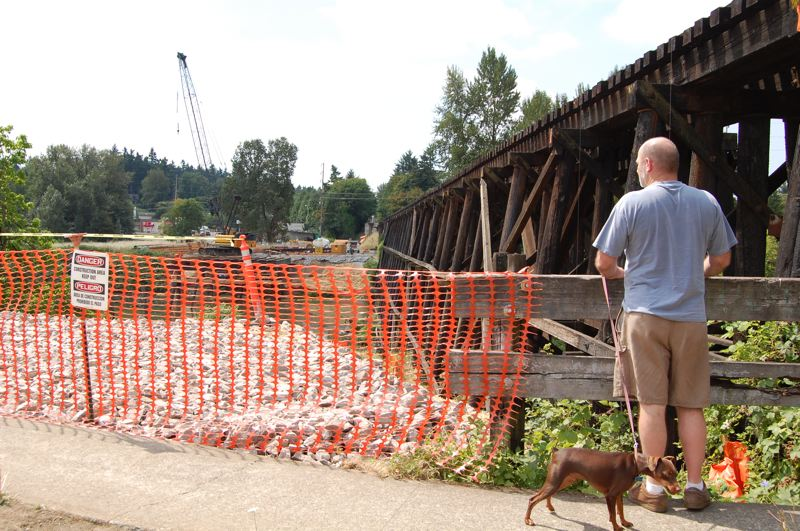 by: PHOTO BY RAYMOND RENDLEMAN - Local residents often stop at the southernmost end of Main Street in Milwaukie to watch the construction of a light-rail bridge across Kellogg Lake.