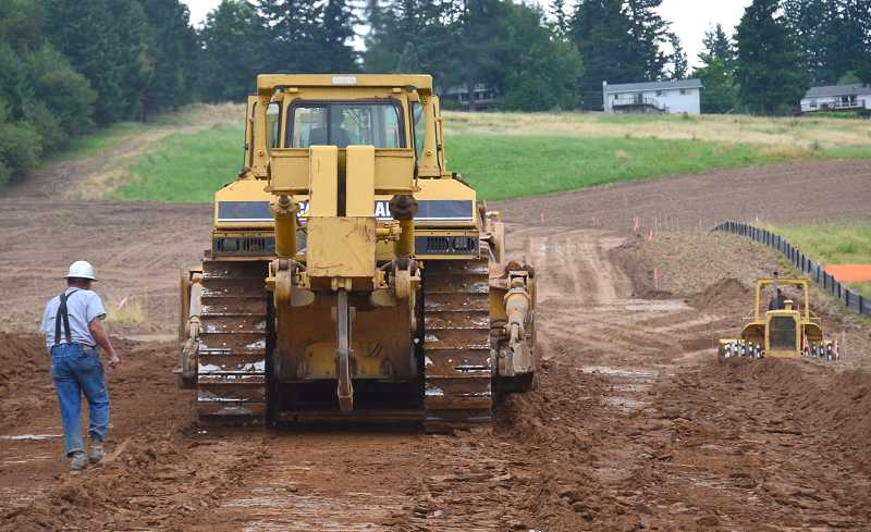 by: VERN UYETAKE - Construction crews work to prepare 12 acres off Rosemont Road in the Stafford area for next year's NW Natural Street of Dreams.