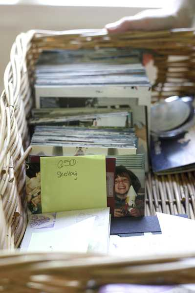by: JONATHAN HOUSE - After she finishes sorting, scanning and creating albums, Rita Norton sends the categorized photos back to her customers.