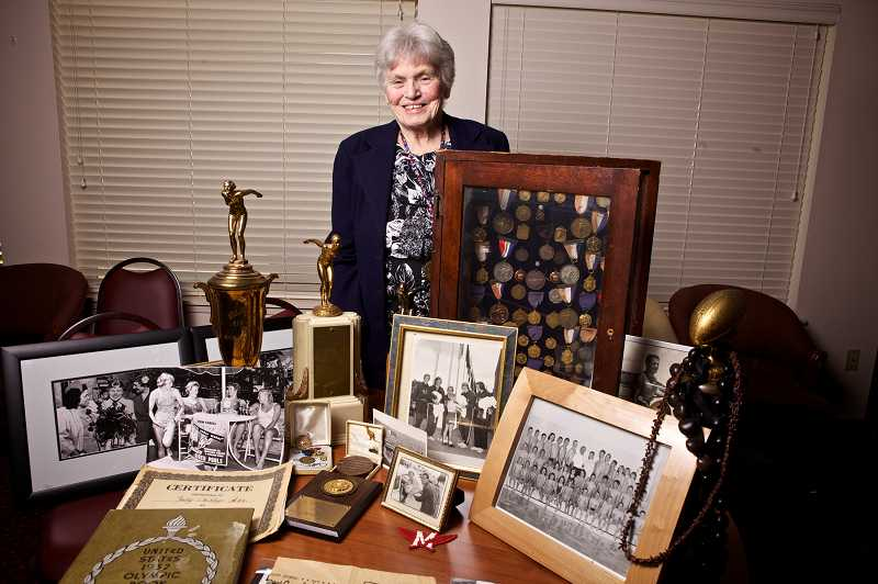 by: JAIME VALDEZ - Judy DeRego stands behind a table full of accolades she won at swimming events years ago.