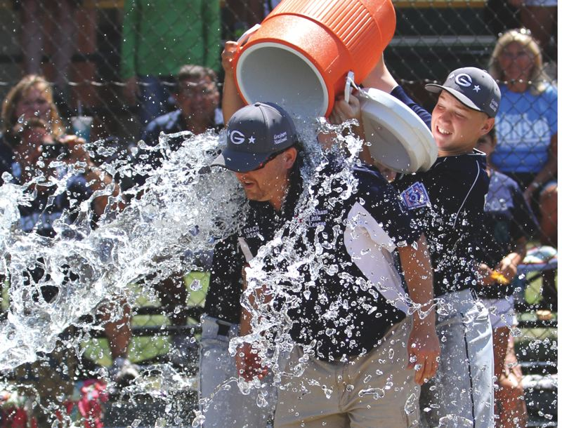 by: CONTRIBUTED PHOTO: DEBBIE MEHLHAFF - Jason Trickel gets dumped with water after the Nationals won the state final last month. He had to postpone starting a new job to continue coaching the team at this weeks Little League World Series.