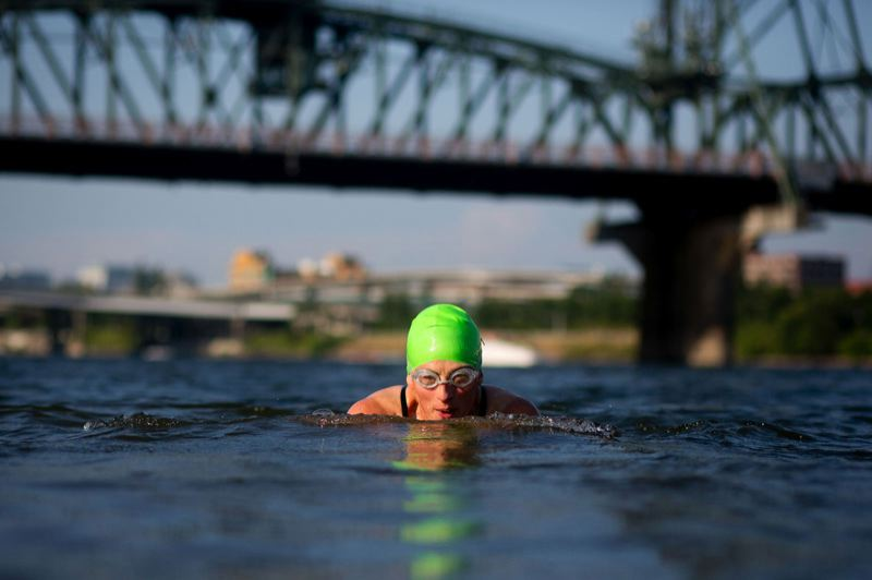 by: CHRISTOPHER ONSTOTT/TRIBUNE PHOTO  - Marisa Frieder swims across the Willamette River toward the Hawthorne Bowl. Volunteers hope to convert the area north of RiverPlace into a more swimmer-friendly beach, by removing the rocks and installing buoys to keep people away from motorized vessels.