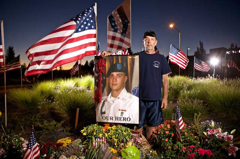 by: JAIME VALDEZ - Jeff Keller stands at a memorial for his son, Army Pfc. Andrew Keller, that friends of the 22-year-old soldier created on the Southwest Barrows Road roundabout near his Tigard home. The 2008 Southridge High School graduate was killed in action on Aug. 15 in Afghanistan.
