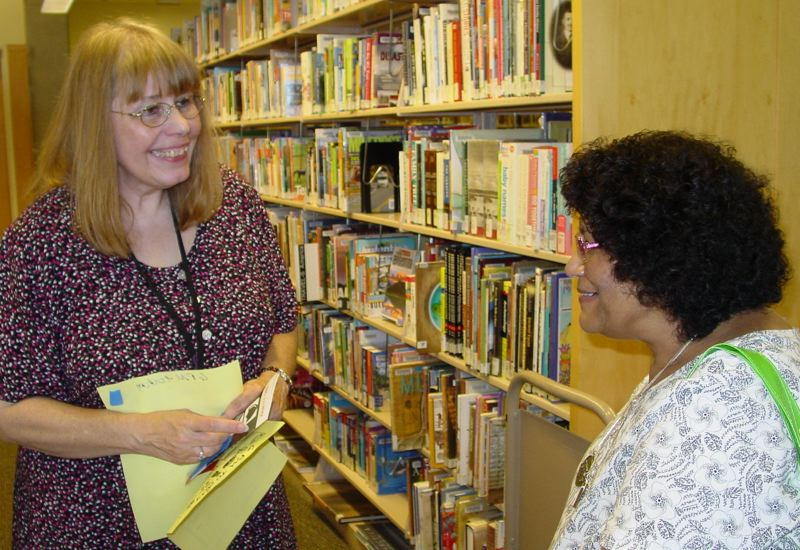 by: MERRY MACKINNON - SHIBA Coordinator Janet Bowman talks with Rita Bhatia at Multnomah County Hollywood Branch Library where Bowman gave a talk on making the most of Medicare.