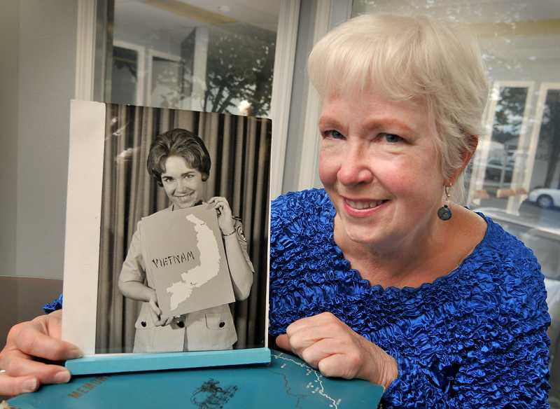 by: VERN UYETAKE - Linda Driscoll displays a photo of herself from back in 1969 when she was serving with the American Red Cross in Vietnam. Her smile is as good as ever.