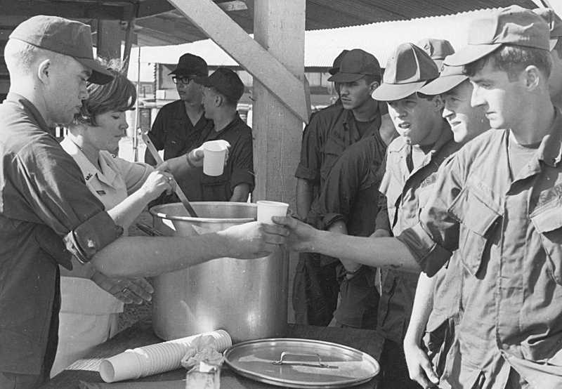 by: SUBMITTED - Linda Driscoll helps serve chow to a group of American servicemen serving in the Vietnam War. As a Donut Dolly, Driscoll also served up smiles, friendliness and fun.